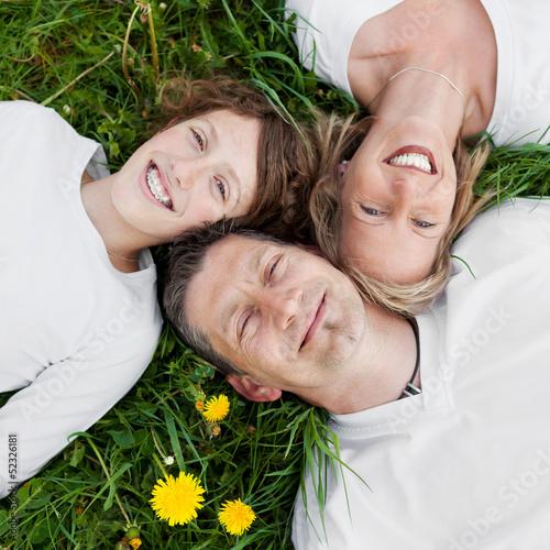 canvas print picture lachende familie liegt im grünen gras