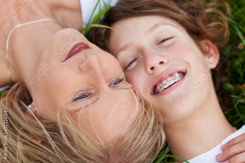 mutter und tochter liegen entspannt im gras