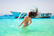Young brunette jumping out of turquoise water of Red Sea, Egypt