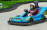Cute Thai girl is driving Go-kart in an amusement park