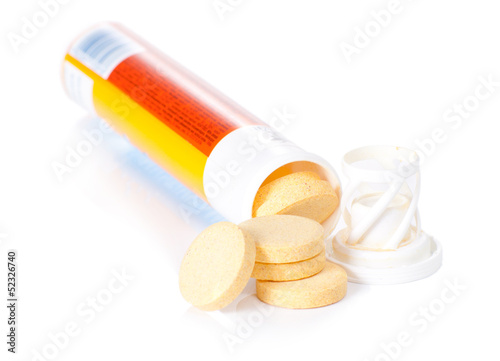 yellow vitamin pills in vial isolated