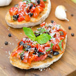 bruschetta with tomato, olives, basil, cheese on a wooden board