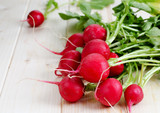 Fresh radishes from ground on old wooden table