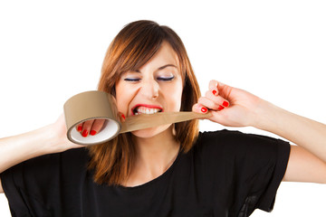 Young woman biting a tape box roll.