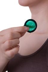 Grünes Kondom vor dem Hals einer jungen Frau
