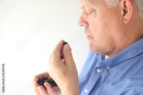 senior man eating blueberries