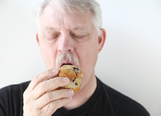 older man with blueberry muffin