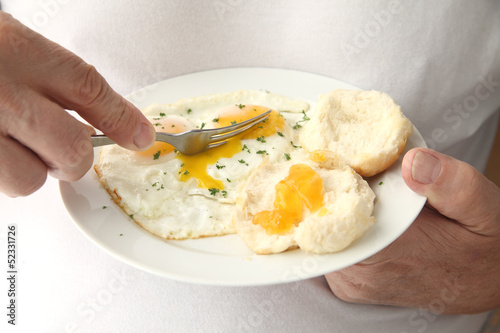 man cutting into fried eggs