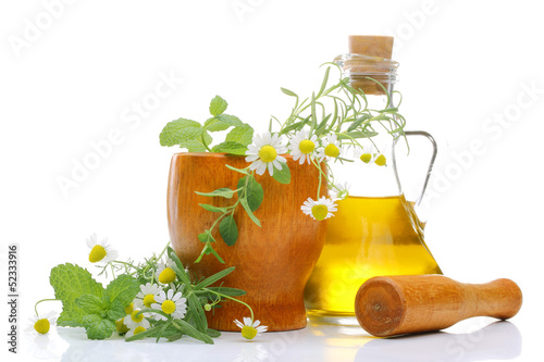 Fresh herbs in wooden mortar with pestlerosemary oil
