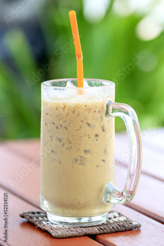 Iced coffee with straw in a glass on the table