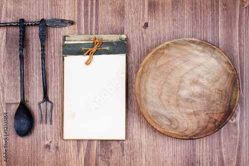 Recipe or menu book, plate, spoon, fork on wood background