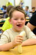 Happy child eating healthy lunch in busy school cafeteria