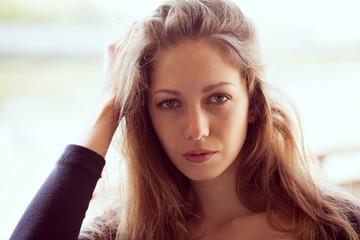 Beautiful young woman straightens long dark hair