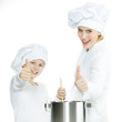 Mother and child having fun in the kitchen, show thumbs up