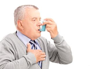 Mature man taking asthma treatment