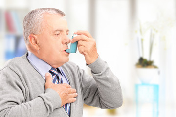 Mature man treating asthma with inhaler