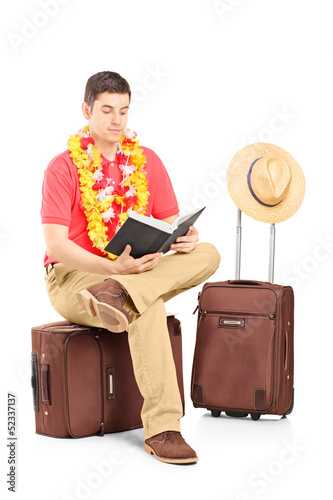 Male tourist sitting on a briefcase and reading a book