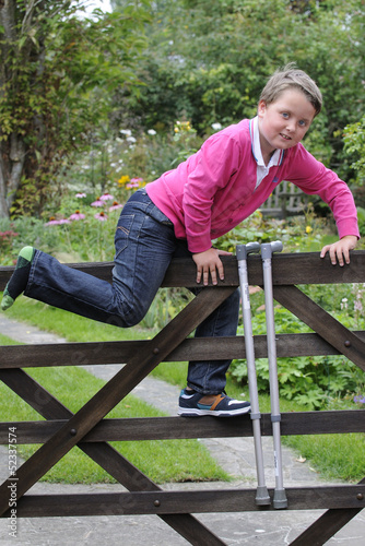Young boy with walking sticks climbing over gate