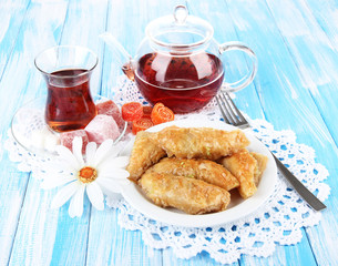 Sweet baklava on plate with tea on table