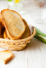 Toasted bread in the bread basket on white boards