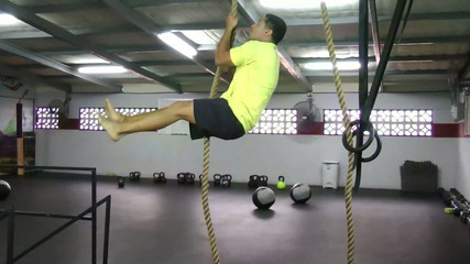 Athlete making leg less rope climb crossfit exercise