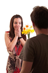 Surprised young woman receiving bouquet of daffodils from her bo