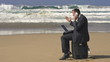 Angry businessman with cellphone on beach, super slow motion