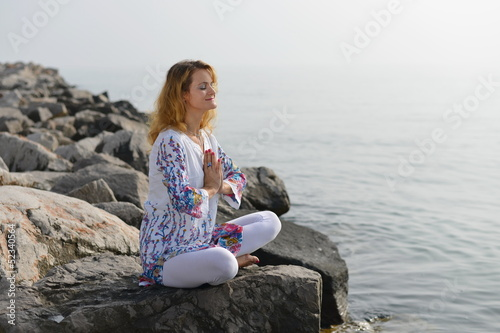 Meditation, Woman on rocky beach in yoga pose