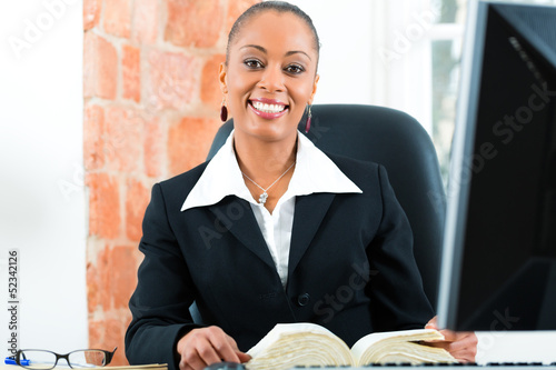 Lawyer in office with law book and computer