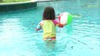 Little girl playing with a colorful ball in the pool