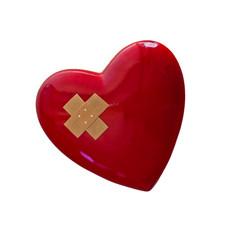 rotes Herz mit Pflaster vor weißem Hintergrund
