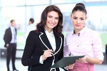 Two business women discussing project and smiling at office