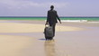 Businessman with suitcase walking on exotic beach, super slow mo