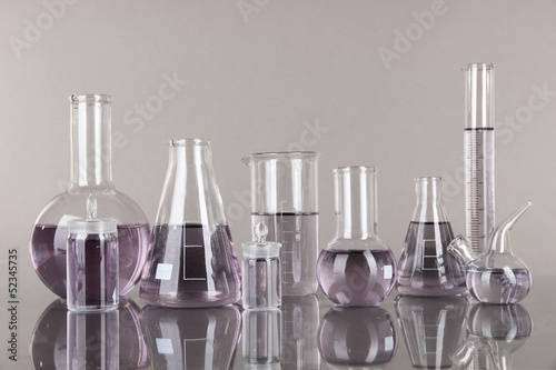 Test-tubes with light purple liquid on gray background