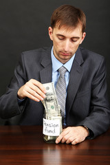 Young businessman with money on black background.