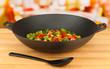 Vegetable ragout in wok, on bright background