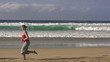 Man and woman jogging on the beach, super slow motion
