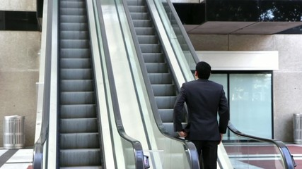 Confident businessman walking to an escalator