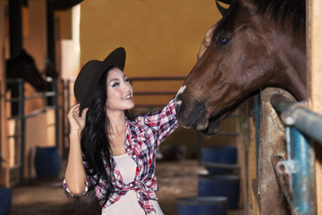 Beautiful female rider and horse at ranch