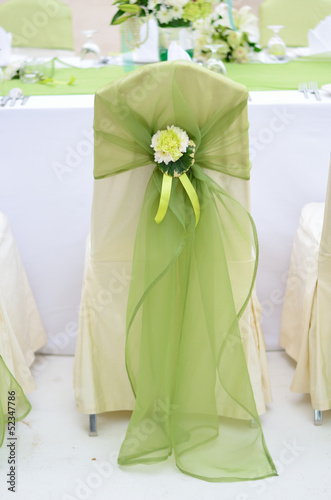 Wedding chair decorated with green color and flower.