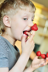 boy is enjoying strawberry