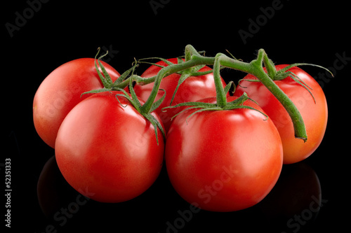 Red tomatoes on a black background