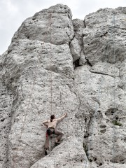 Young man climbing on limestone wall