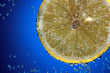 Slice of fresh lemon in water with air bubbles