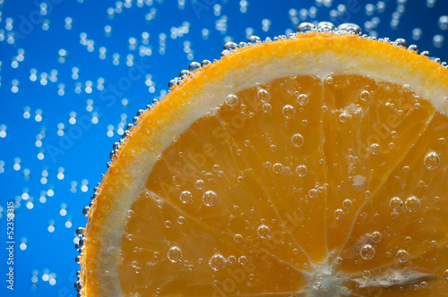 Slice of orange in water with air bubbles