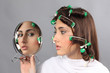 girl with hair curlers and mirror