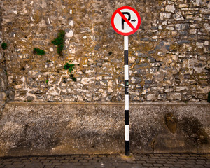 European no parking sign against rough stone wall