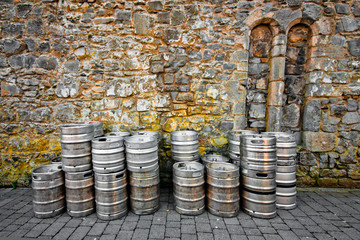 Stack of beer kegs against a rustic stone wall