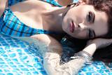 Pretty woman in white bikini floating in swimming pool
