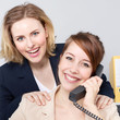 Two business women work in the office as a team